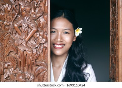 Indonesian young girl in a traditional costume and with a flower in her hair smiles.