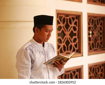 Indonesian young man with sarong reading the Holy Qoran at mosque. Man moslem with holding the Al quran. Muslim hand reading holy quran