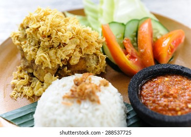 Indonesian-style fried chicken, known as lalapan, served with rice, sambal and vegetables.