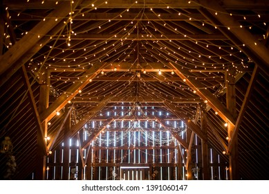 Indoor barn wedding with beautiful cafe string lighting in elegant setting to celebrate marriage of love in a rustic setting