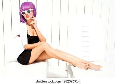Indoor bright fashion summer portrait of stylish  hipster woman, showing her tongue, have long legs and cool bright wig,wearing sneakers bikini pants and young sunglasses.