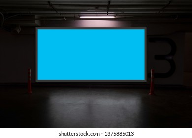 indoor car parking and empty blue billboard .Blank space for text and images.