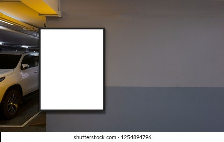 indoor car parking and empty white billboard .Blank space for text and images.