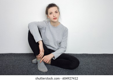 Indoor close up portrait of charming young lady of European appearance wearing grey sweatshirt, black jeans sitting grey carpet against white wall background. Emotions and facial expression concept