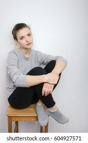 Indoor close up portrait of charming young lady of European appearance wearing grey sweatshirt, black jeans sitting on stool against white wall background. Emotions and facial expression concept