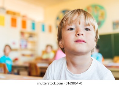 Indoor close up portrait of a cute little boy in a classroom.