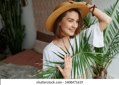 Indoor close up portrait of elegant pretty woman in straw hat and white blouse posing at home. Home plants and palms.