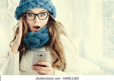 Indoor close up portrait of young beautiful surprising girl looking at camera and holding smartphone. Model expressing joy and excitement. Woman wearing eyeglasses, trendy blue accessories. Copy space