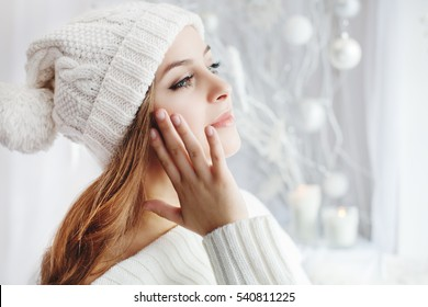 Indoor close up portrait of young beautiful girl touching her face by hand, looking aside. Model wearing winter hat and sweater. Day light from window, white room as background. Copy space for text