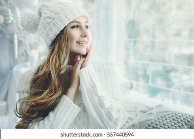 Indoor close up portrait of young beautiful happy smiling girl touching her face, looking aside. Model wearing stylish clothes. Day light from window, white room as background. Copy space for text.