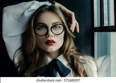 Indoor close up portrait of young beautiful fashionable business woman posing on dark background, near window. Model looking at camera. Lady wearing stylish eyeglasses. Female fashion, beauty concept