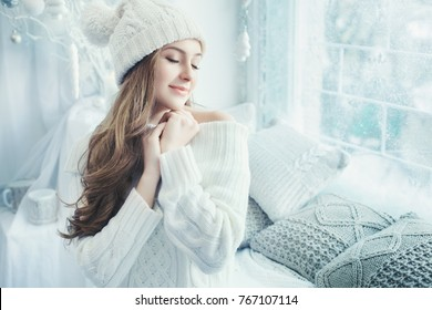 Indoor close up portrait of young beautiful happy smiling girl touching her face. Model wearing stylish clothes. Day light from window. Female beauty, fashion concept. Copy space for text.