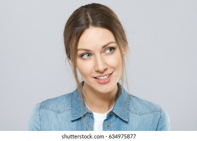 Indoor closeup of attractive female isolated on gray background looking rightwards with happy interested smile and big green eyes showing attention, curiousity and wiilingness to learn secret.