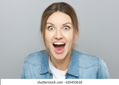 Indoor closeup of extremely emotional European woman isolated on grey background looking crazy with opened eyes, shouting desperately in happiness and euphoria having learnt favorable things.