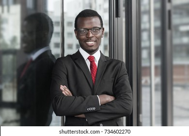 Indoor closeup of handsome African company leader wearing dark suit, white shirt and tie, looking straight at camera through eyeglasses with arms crossed, showing confidence in business development