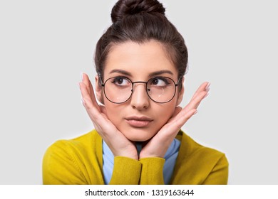 Indoor closeup image of brunette woman in bun hairstyle, wearing casual outfit and spectacles, leaning her face on palms while standing over white wall and looking at one side. People, emotion concept