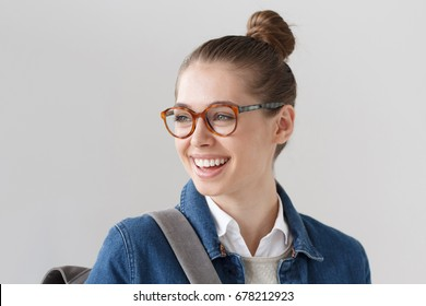 Indoor closeup of nice teenager girl wearing big trendy spectacles and denim jacket isolated on gray background, turned leftwards with gray backpack on her back, laughing and smiling happily.