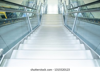Indoor Concrete Staircase beside escalator at airport terminal.