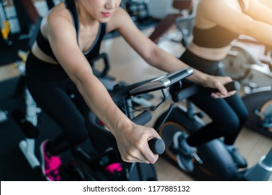 Indoor cycling women doing HIIT cardio workout biking on indoors gym bike