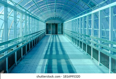 Indoor elevated pedestrian bridge in the city, the view from the inside. Tunnel for safe crossing of the road with a roof made of blue plastic that protects pedestrians from wind, rain and snow