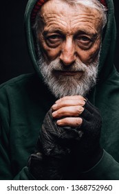 Indoor face portrait of old-aged homeless hobo man dressed in green hoodie with hood on head breathing on hands in diverse mittens to keep them warm at cold day.