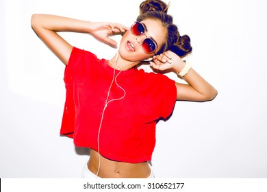 Indoor fashion autumn portrait of elegant sexy woman in luxury bright glamour outfit,red lips,red crop top and trendy sunglasses.Model holding earphones,listen music,ponytail.smiley woman,crazy,toned