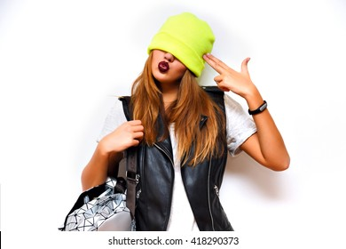 Indoor fashion grunge portrait of cheeky hipster girl ,leather jacket, rock style, dark lips, flash, white background, crazy emotions. Put hat on her eyes, imitating gun by her hand, angry, evil.
