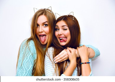 Indoor fashion lifestyle portrait of pretty teen happy friends girls, hugs, wearing cozy pastel cashmere mint sweaters, brunette and blonde hairs, make up, trendy accessory, showing long tongue, crazy