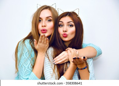 Indoor fashion lifestyle portrait of pretty teen happy friends girls, hugs, wearing cozy pastel cashmere mint sweaters, brunette and blonde hairs, make up, trendy accessory, sending air kiss.