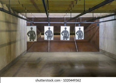 Indoor Firearm shooting range wide shot with four paper targets