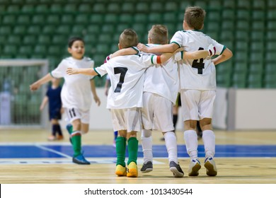 Indoor football soccer match for children. Happy kids together after winning futsal game. Children celebrate sport victory. Youth sport triumph in futsal. Futsal indoor soccer tournament for kids