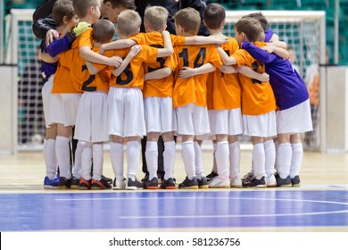 Indoor football soccer match for children. Coach giving young soccer futsal team advices. Youth soccer team before final game. Football match for children. Coach briefing. Soccer football background.