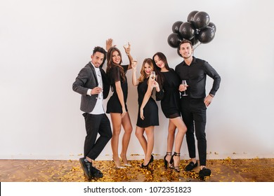 Indoor full-length portrait of confident stylish man with party balloons behind. Joyful african guy chilling with university friends at home and celebrating the end of exams.