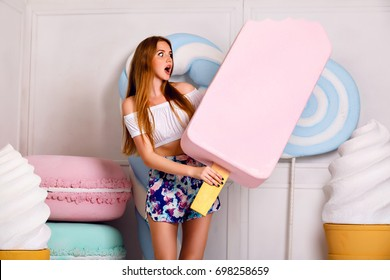 Indoor funny image to young blonde woman holding gigant pink ice-cream, surprised crazy emotions, long hairs natural make up, big sweetness, french macaroons and lollipops.