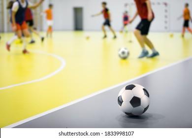 Indoor futsal soccer players playing futsal training. Indoor soccer sports hall. Futsal players kicking ball. Futsal training dribbling drill. Sports background. Indoor soccer league