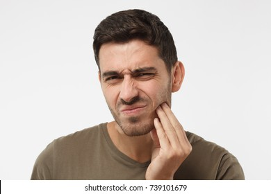 Indoor headshot of young male feeling pain, holding his cheek with hand, suffering from bad toothache, looking at camera with painful expression. Tooth ache concept.