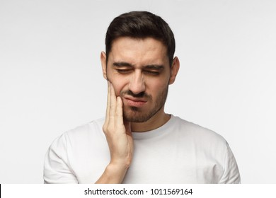 Indoor headshot of young man feeling pain, holding his cheek with hand, suffering from bad toothache, looking at camera with painful expression. Tooth ache concept.
