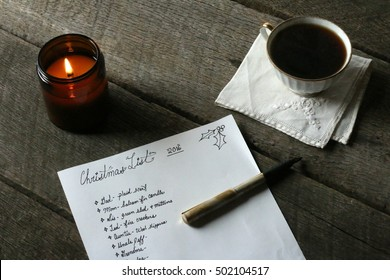 Indoor Holiday Scene With Christmas List And Pen Laying On Dark Hardwood Table With Black Coffee On Linen Napkin And All Natural Soy Candle Lit And Glowing