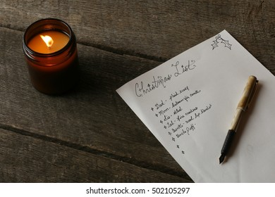 Indoor Holiday Scene Of Handwritten Christmas List And Pen Laying On Dark Hardwood Table With All Natural Soy Candle In Brown Glass Jar Lit And Glowing
