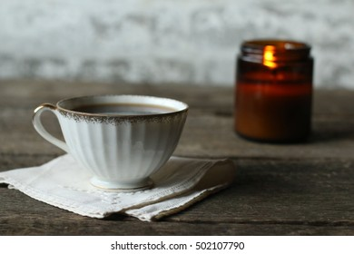 Indoor Holiday Scene Of Hot Black Coffee And All Natural Soy Candle Lit And Glowing On Dark Hardwood Table With Stone Background