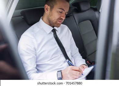 Indoor horizontal portrait of a Caucasian businessman with papers writing some news and sitting on car back seat. Handsome business man wearing white shirt in black tie in vehicle .