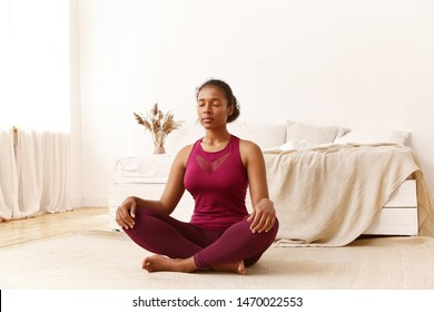 Indoor image of athletic young dark skinned female in stylish sportswear sitting on floor in half lotus pose, closing eyes, practicing yoga and meditation, having peaceful calm facial expression