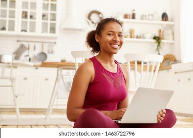 Indoor image of cute cheerful young African woman in sportswear sitting on floor in kitchen holding portable computer, smiling broadly at camera, watching video course on pilates or yoga online