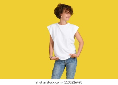 Indoor isolated shot of beautiful stylish woman with shaggy haircut wearing oversize white t-shirt and posing at yellow studio wall with copy space for your advertising concept. Look aside. Youth