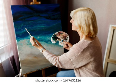 Indoor lifestyle portrait of mature woman draws with acrylic on canvas. Staying at home.