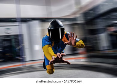Indoor. Man fly in wind tunnel. Indoor skydiving in blue yellow suit. New fly sport.