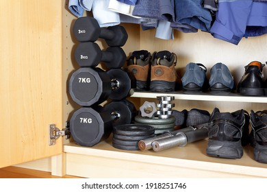Indoor and oudoor sports equipment for the covid pandemic: weights, dumbbells, running shoes and hiking boots at the bottom of a wardrobe