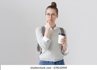 Indoor photo of beautiful young female in big round eyeglasses isolated on grey background with bag on her back, scratching chin with doubtful facial expression as if thinking how to find solution.