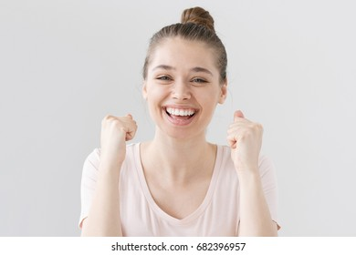 Indoor photo of good-looking teenage girl isolated on gray background celebrating victory and acting as if she is winner, squeezing fists in deep emotional expression of happiness, luck and content.