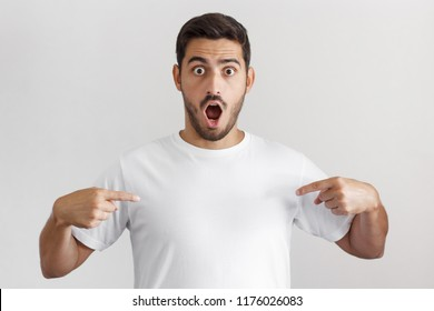 Indoor photo of handsome Caucasian male isolated on gray background wearing white blank T-shirt and pointing to it with both hands with mouth opened with surprise, amazed by good commercial offer